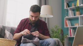 Tiro médio do homem que senta-se no sofá e no curso de confecção de malhas de observação no portátil