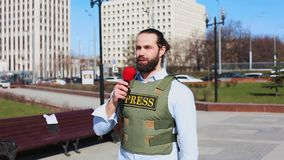 Tiro médio, journalista masculino da televisão em um revestimento à prova de balas que fala a um microfone na frente dos arranha- filme