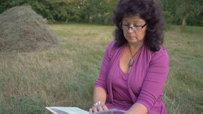 Tiro médio, vidros vestindo da mulher idosa, girando a página de um livro e de uma leitura pensativa, assento em um esclareciment filme
