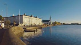 Tiro móvil, caminando a lo largo del lago Tjornin de la orilla en el centro de Reykjavik en día soleado almacen de video