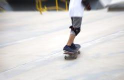 Tiro móvil del enfoque del sketeboard con la pierna del niño Imagen de archivo libre de regalías