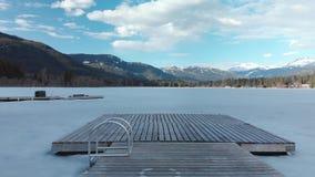 Tiro móvil delantero de un pequeño muelle de madera en alfa congelada del lago en marmota, A.C., Canadá almacen de metraje de vídeo