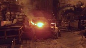 Tiro móvil en la fundición en planta metalúrgica, fuego abierto y metal candente en horno metrajes