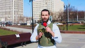 Tiro m?dio, journalista masculino da televis?o em um revestimento ? prova de balas que fala a um microfone na frente dos arranha- vídeos de arquivo