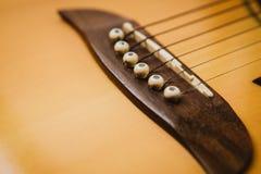 Tiro macro abajo del fretboard de la guitarra acústica con la profundidad del campo baja Imagenes de archivo