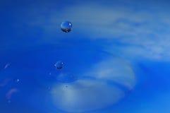 Tiro macro da gota da água que cai na água azul Foto de Stock