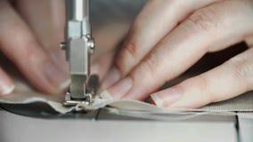 Tiro macro das mãos fêmeas que trabalham na máquina de costura Desenhista do conceito da jovem mulher que trabalha em uma máquina vídeos de arquivo