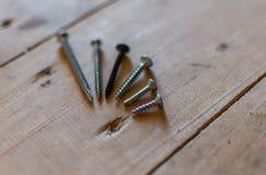 Tiro macro de diversos tornillos en banco de madera Foto de archivo