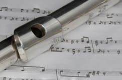 Tiro macro de la flauta en partitura Imagenes de archivo