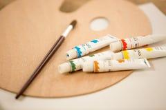 Tiro macro de los tubos de la pintura de aceite una brocha que miente en la plataforma Imagen de archivo