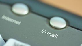 Tiro macro de un finger que empuja el botón del correo electrónico en un teclado metrajes