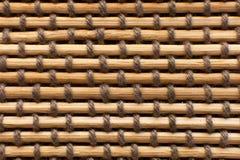 Tiro macro de una estera de bambú ligada con los cordones tejidos entre los palillos foto de archivo libre de regalías