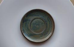 Tiro macro del pequeño platillo azul en una placa blanca grande en una tabla de madera Imágenes de archivo libres de regalías