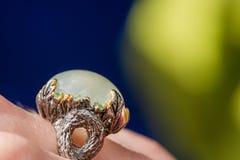 Tiro macro do anel de noivado de prata no fundo colorido, efervescente Imagem de Stock