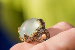 Tiro macro do anel de noivado de prata no fundo colorido, efervescente Imagens de Stock