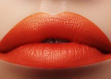 Tiro macro do close-up da boca fêmea Composição vermelha dos bordos do encanto 'sexy' com gesto da sensualidade Cor alaranjada fotos de stock royalty free