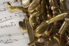 Tiro macro do saxofone do conteúdo na partitura Imagem de Stock Royalty Free