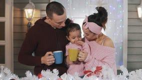Tiro medio de la familia feliz que abraza en el pórtico de la Navidad con el chocolate caliente almacen de metraje de vídeo
