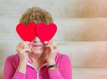 Tiro medio de la mujer caucásica envejecida centro que lleva a cabo corazones de papel rojos sobre sus ojos mientras que se sient foto de archivo libre de regalías
