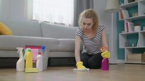 Tiro medio de la mujer en guantes amarillos con el piso de la limpieza del paño en sala de estar almacen de metraje de vídeo