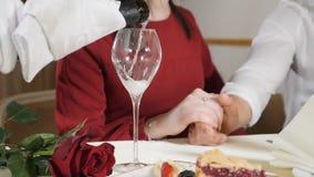 Tiro medio de las manos jovenes de los pares en la tabla Cámara lenta de los pares de amor de Pouring Champagne To del camarero q almacen de metraje de vídeo