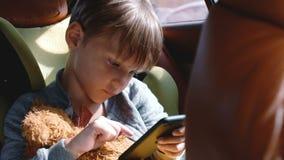 Tiro medio de poco muchacho caucásico feliz de 4-6 años que usa smartphone en asiento de la seguridad del niño del coche con un j metrajes