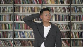 Tiro medio del hombre asiático joven que elige un libro que rasguña su cabeza metrajes