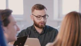 Tiro medio del hombre de negocios caucásico profesional joven que habla con los colegas detrás de la tabla en la reunión del equi almacen de metraje de vídeo