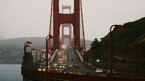 Tiro medio del lapso de tiempo de los semáforos de coche en puente Golden Gate icónico en la puesta del sol San Francisco Califor almacen de video