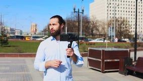 Tiro medio, reportero de televisión de sexo masculino que habla con un micrófono delante de rascacielos en el distrito financiero almacen de metraje de vídeo