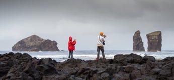 Tiro panorámico de un par de turistas, fotografiando la playa volcánica de Mosteiros imagen de archivo