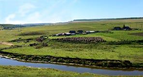 Tiro panorámico del campo En un día de verano soleado Pueblo en los bancos del río Imagen de archivo libre de regalías