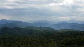 Tiro panorâmico aéreo do zangão que filtra direita para a esquerda das montanhas com nuvens video estoque
