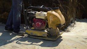 Tiro parcial del hombre que trabaja con el compresor de la placa vibrante en superficie de la arena almacen de metraje de vídeo