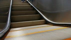 Tiro próximo da escada rolante elétrica com partes de uma pessoa que vai para baixo filme