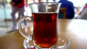 Tiro próximo do vidro turco tradicional do chá em um restaurante na tabela com os povos no fundo filme