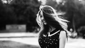 Tiro preto e branco da mulher de cabelos compridos bonita nova na cidade fotografia de stock
