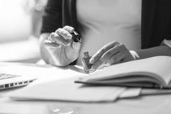 Tiro preto e branco das unhas da pintura da mulher de negócios no wo Fotografia de Stock