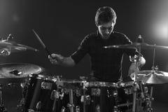 Tiro preto e branco do baterista Playing Drum Kit In Studio foto de stock