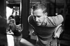 Tiro preto e branco do homem que exercita com anéis ginásticos imagens de stock royalty free