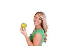 Tiro principal da mulher que mantém uma maçã contra o fundo branco Imagens de Stock