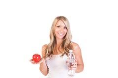 Tiro principal da mulher que mantém uma maçã e uma água contra o fundo branco Fotos de Stock Royalty Free