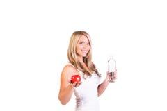 Tiro principal da mulher que mantém uma maçã e uma água contra o fundo branco Imagens de Stock