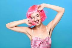 Tiro principal de la belleza La mujer joven con arte pop creativo compone y pica la peluca que mira la cámara en fondo azul Foto de archivo