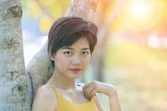 Tiro principal del retrato de la mujer hermosa asiática joven en parque Foto de archivo