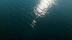 Tiro que está en órbita de un solo kajak en el agua en ensenada profunda almacen de metraje de vídeo