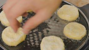 Tiro rápido - cozinheiro que prepara panquecas de um queijo em uma bandeja quente com óleo filme