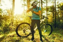 Tiro raro do ciclista que veste a roupa de ciclagem preta e para vestir o capacete protetor durante o exercício nas madeiras Povo imagens de stock