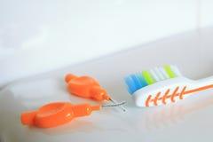 Tiro raso do DOF de uma escova de dentes e de umas escovas interdental em uma superfície brilhante fotos de stock