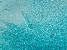 Tiro a?reo de nadadores en una playa hermosa con agua azul y la arena blanca - agua profunda imagenes de archivo